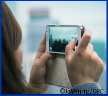 Woman taking city picture with her smartphone.